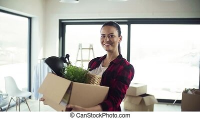 A cheerful young woman moving in new home, holding a box.