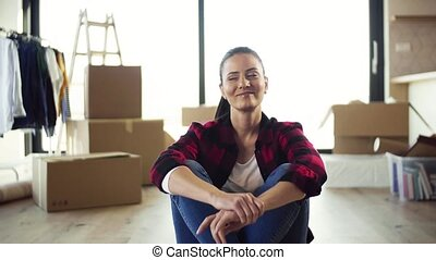 A cheerful young woman moving in new home, resting.