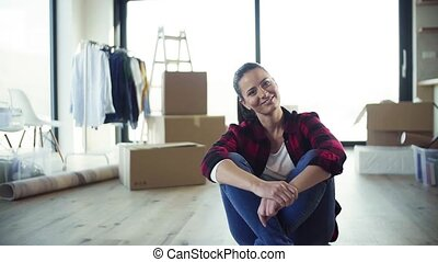 A cheerful young woman moving in new home, resting. Slow motion.