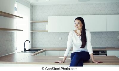 A cheerful young woman sitting on kitchen counter in new home, resting.