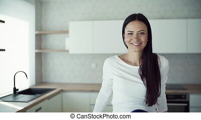 A cheerful young woman sitting on kitchen counter in new...