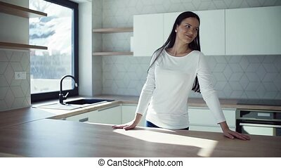 A cheerful young woman standing in kitchen in new home, resting.