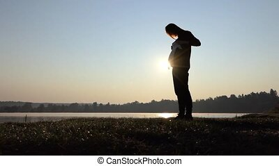 a Cheery Pregnant Woman Plays With Baby's Bodysuit at Sunset in Autumn