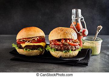 A cheese burger on a plain bun beside dip