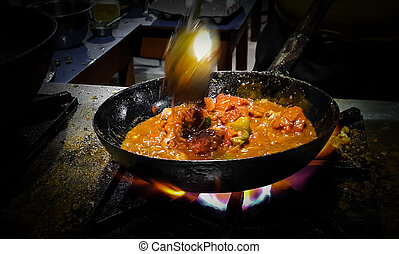 a chef cooking tadka fry in a frying pan at a road side food...