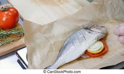 A chef in the restaurant kitchen prepared the fish for...