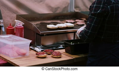 A chef in white gloves makes burger with fresh salad and grilling raw meats for hamburgers on the grill. Back view