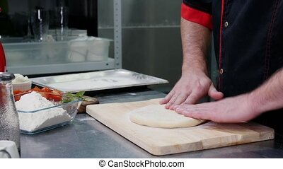 A chef preparing a dough for the pizza with rolling it in...