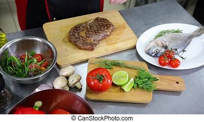 A chef working in the kitchen. A man about to cut the meat steak