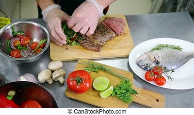 A chef working in the kitchen. A man serving a steak with salad