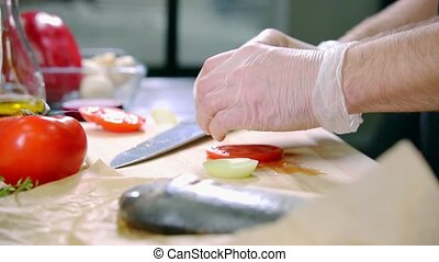 A chef working in the kitchen. Connecting vegetables for the fish filling