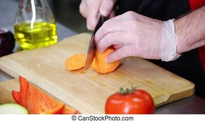 A chef working in the kitchen. Cutting the carrot