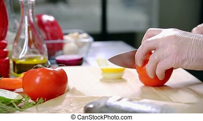 A chef working in the kitchen. Cutting the tomato