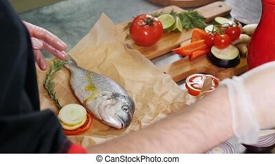 A chef working in the kitchen. Greasing the fish with an...