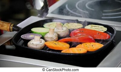 A chef working in the kitchen. Heating up the mushrooms and vegetables in the pan without an oil