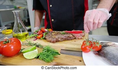 A chef working in the kitchen. Making a salad garnish to the...