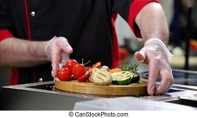 A chef working in the kitchen. Serving fried vegetables on a wooden desk