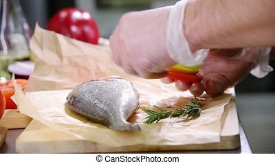 A chef working in the kitchen. Stuffing the fish with onion and tomato