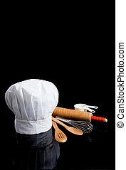 A chef's toque with kitchen utensils on black