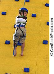 A child abseilling down a climbing wall