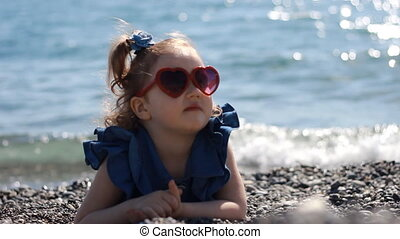 A child by the sea on a pebble beach on a windy sunny day with glasses in the form of a heart