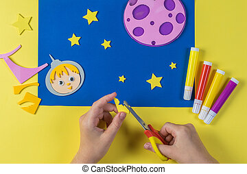 A child carves yellow stars for crafts on the theme of space.