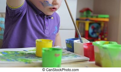 A child draws with colored paints while sitting at table