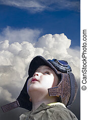 A child dressed in pilot looking into the blue sky