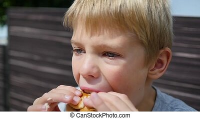 A child eats a bun with a cutlet and cheese in a fast food restaurant