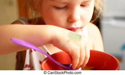 A child eats honey with a spoon from a plastic jar 4k