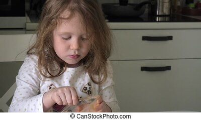 A child eats honey with a spoon from a plastic jar
