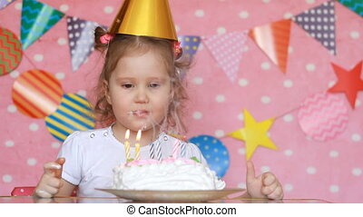 A child girl blows out candles on a birthday cake and eats...