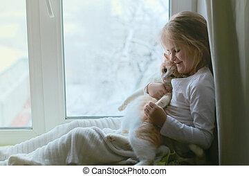 A child hugs a cat sitting on a windowsill