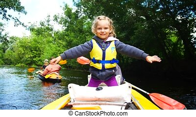 A child in a kayak on the river. Family outdoor activities....