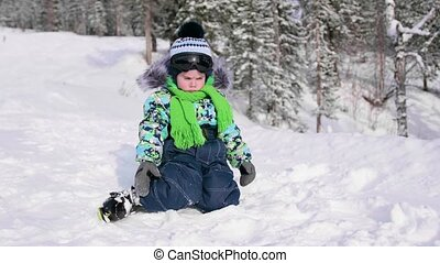 A child in a winter Park sitting on the snow. Walking in the fresh air. Healthy lifestyle
