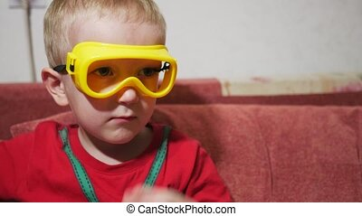 A child in safety glasses sits on the sofa at home and watches TV.