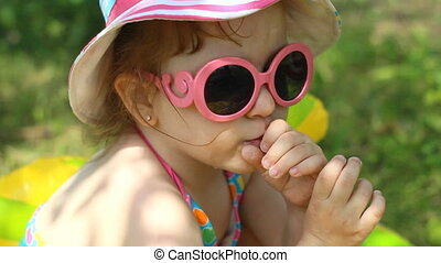A child in sunglasses on a sunny day. looks at the camera. Close up