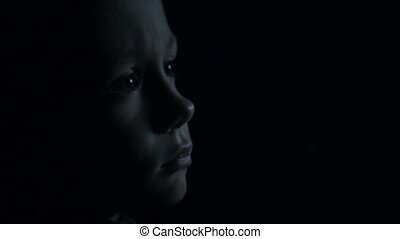 A child in the dark is watching TV - Little boy at night...