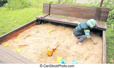 A child in the kindergarten playing in the sandpit HD...