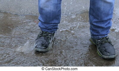A child in winter boots jumping in a puddle - A boy in...