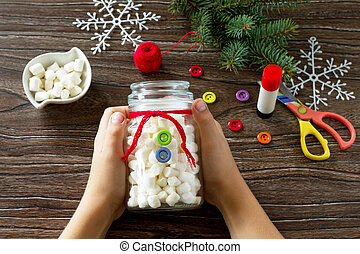 A child is making a Christmas present with a snowman of sweets. Made by own hands. Children's art project for children. Craft for kids. Copy space for text.