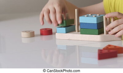 A child is playing a logical wooden toy. The concept of early child development, wooden educational toys.