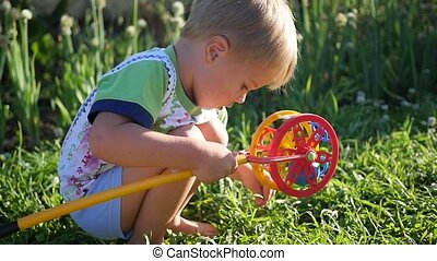 A child is playing with a toy on the lawn. Entertainment and outdoor games
