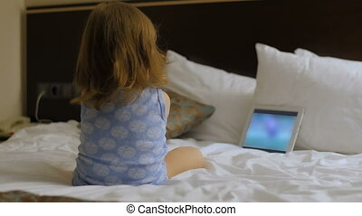 A child is sitting in the bedroom on the bed looking at the phone, tablet, computer.
