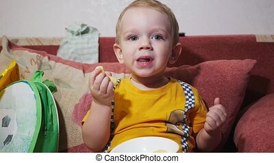 A child is sitting on the sofa at home and watching TV. Eat corn sticks and smile