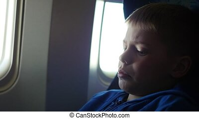 A child looking out the window of an airplane on a sunny day