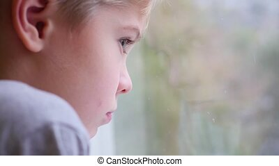 a child looks out the window at the snowfall closeup
