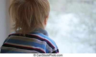 a child looks out the window at the snowfall