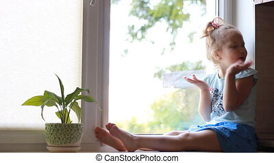 A child looks out the window, smiling, showing no gesture....