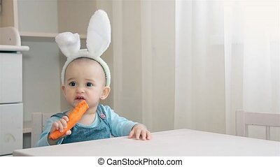 A child of preschool age with Bunny ears on his head sitting in the nursery and chews orange carrot